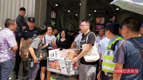 """开业首日人潮汹涌,早到的市民推着装满""""战利品""""的购物车走出卖场。《中国经济周刊》记者  王雨菲 摄"""