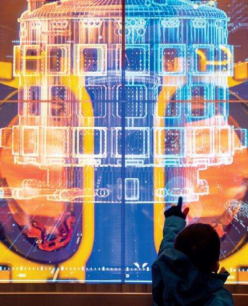 """p14-22019 年11 月22 日,一名小朋友在""""伟大的变革——庆祝改革开放40 周年大型展览""""上观看国际热核聚变实验堆模型。"""