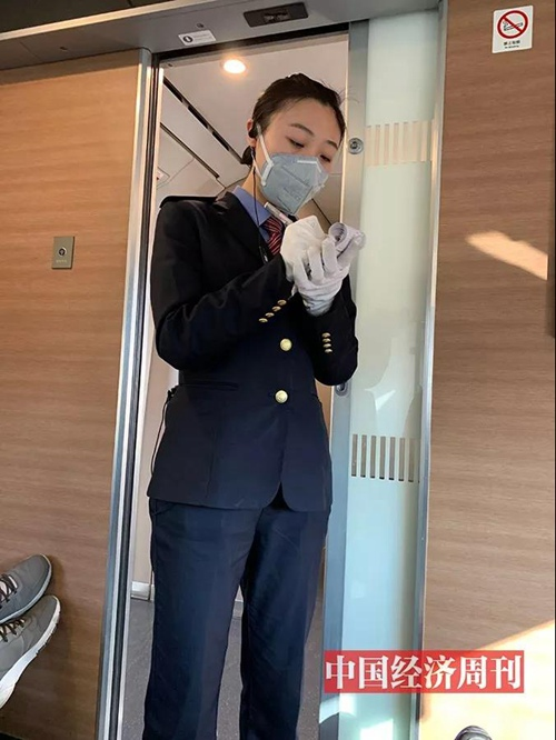 高铁列车上,乘务员佩戴双层手套为旅客服务。