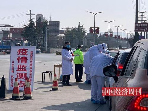 平陆县城高速路口,工作人员测量体温并登记。