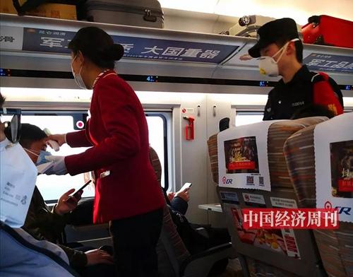 列车员为乘客检测体温。