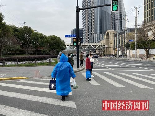 3月3日上海多云,出门买菜的上海市民把雨披当作防护服。(宋杰摄影)