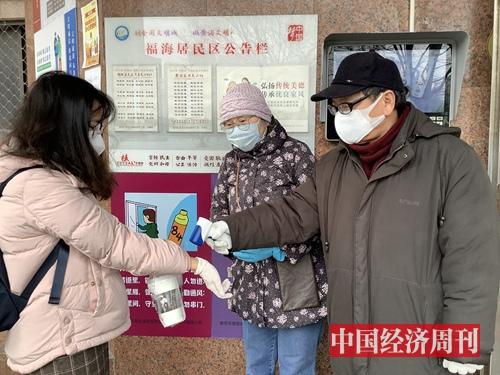 复工后,上海商住小区加强防控管理,志愿者在业委会主任带领下每天早上为务工人员测温。(宋杰摄影)