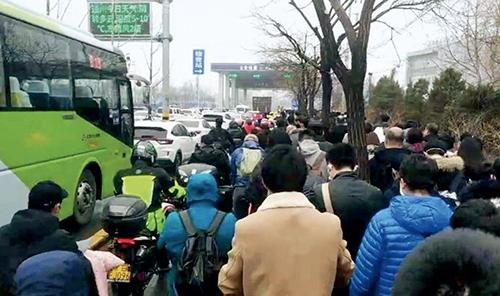 p43-2 3 月9 日,818 路和拥挤的人群一起在等待白庙北综合检查的放行。