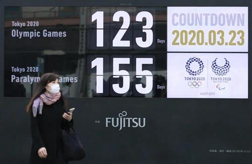 3月23日,一名行人戴着口罩在日本东京新桥地区经过显示东京奥运会和残奥会倒计时的大屏幕。图片来源:新华社