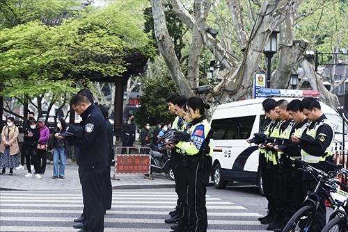 4月4日上午,在过往人流如织杭州西湖断桥边,杭州西湖旅游警察对抗击新冠肺炎疫情斗争牺牲烈士和逝世同胞进行哀悼 人民视觉