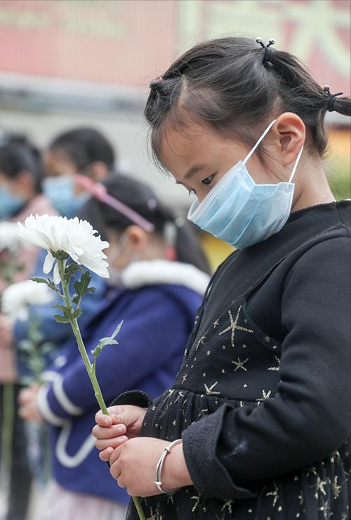 4月4日,四川华蓥,孩子们手捧鲜花在华蓥山广场向抗击新冠肺炎疫情斗争牺牲的烈士和逝世同胞及革命先烈默哀 人民视觉