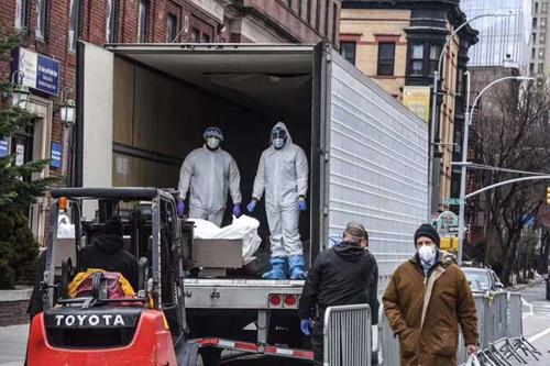 醫院路邊停放的冷藏式卡車臨時停尸房,叉車把尸體送入卡車保存,叉車工人在接受媒體采訪時說他正在做他所能做的一切。(楊競博供圖)