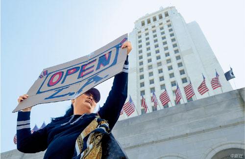 """P962020 年4 月22 日,美国加利福尼亚州洛杉矶市,一名示威者在洛杉矶市中心市政厅前手持""""开放洛杉矶""""的标语。"""