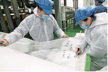 33 2020年4月8日,工人在北京燕山石化生产出的KN95口罩专用熔喷布上做标记。