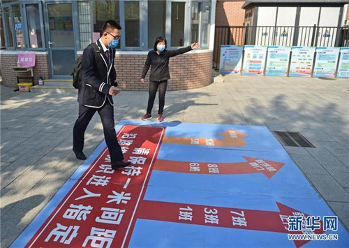 4月27日,在北京市廣渠門中學,一名高三年級的學生按路面指示圖引導前往教室。當日,北京市高三年級學生開學復課。新華社發(陳鐘昊攝)