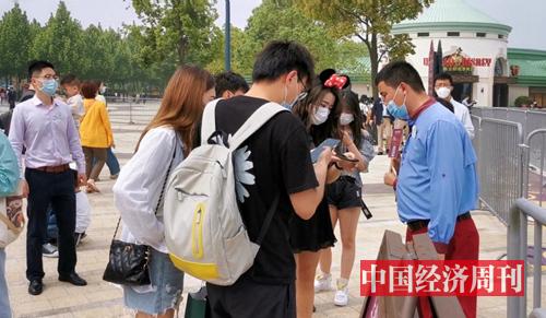 入园前正在操作手机生成预约码的游客 摄影 中国经济周刊记者 王雨菲