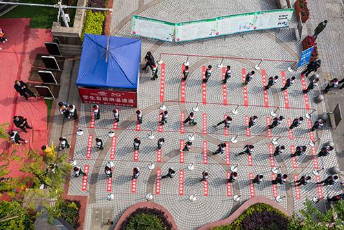 34-1 四川绵阳御营小学在校门处画好了体温测试线,学生有序进入。
