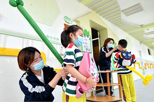 """35-1 浙江湖州某幼儿园,教师正在为排队的孩子安装""""一米尾巴"""",保持安全距离。"""