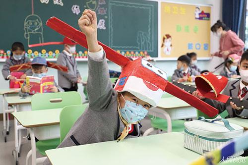 """35-2 浙江某小学提出""""头戴一米帽、保持一米距""""的倡议,要求小朋友们争取戴一天帽子不坏,不能碰到别人。"""