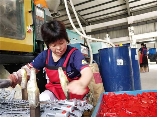 旌德县孙村镇就业扶贫基地——旌德县电子电器厂安全帽生产车间,本地女工正在组装安全帽固定带。