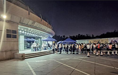 46-1 6 月16 日晚11 點,北京市海淀區一處核酸檢測點,市民排隊參加核酸檢測。