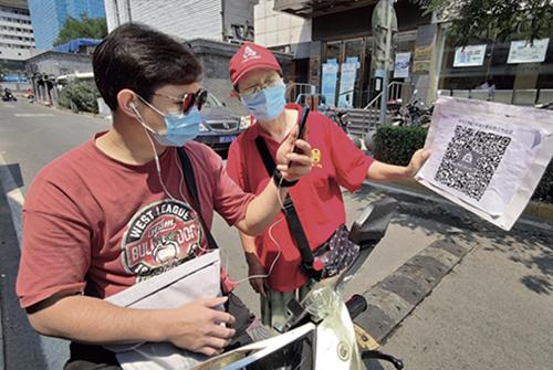 46-2 6 月19 日,京城市民烈日下站崗值班防控疫情。