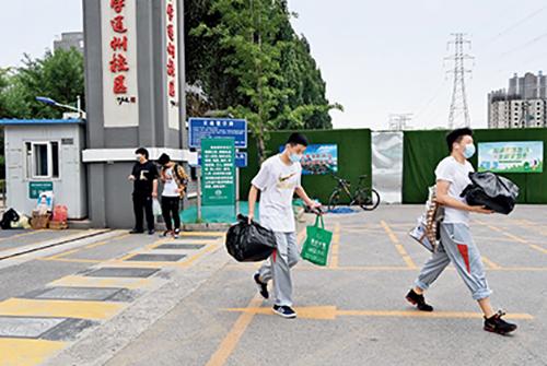 47-1 6 月17 日,北京中小學各年級一律停止到校上課,學生陸續來到學校取回自己的物品。