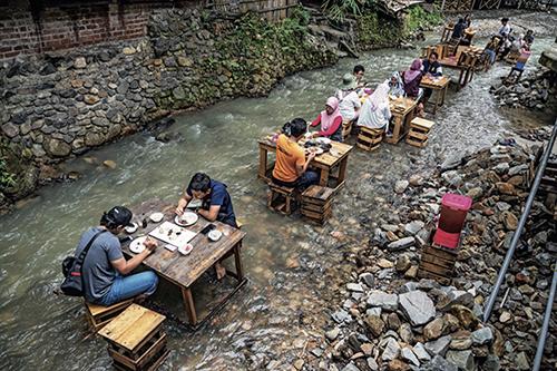 46-1当地时间2020年7月14日,马来西亚吉隆坡,当地人在河边的餐馆外吃午饭。