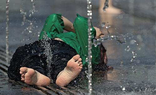47-1当地时间2020年7月11日,俄罗斯莫斯科迎来高温天气。一名女子躺在喷泉池里降温。