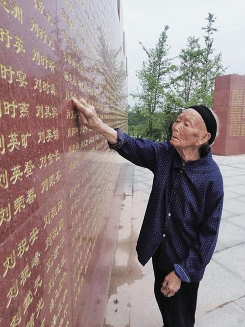 17 103 岁高龄的段桂秀是赣州地区唯一还健在的红军烈士遗孀,在烈士纪念碑前寻找丈夫王金长的名字。