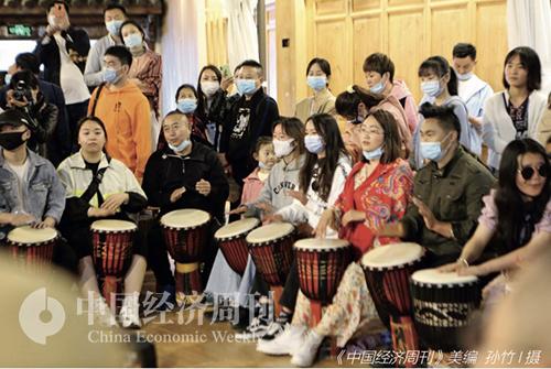 54-2 4月3日,云南丽江古城晚间,街头艺人教授手鼓弹唱,引来众多游客驻足。《中国经济周刊》美编