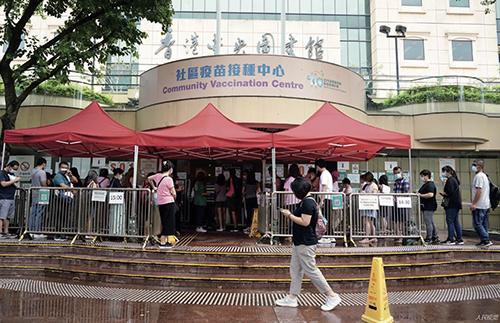 82 5 月29 日下午,眾多市民在位于香港中央圖書館的社區疫苗接種中心門口排隊等候接種新冠疫苗。
