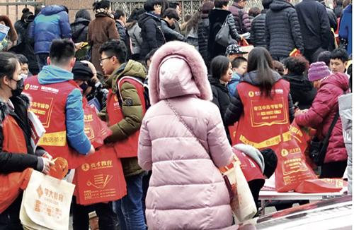 33-1 大连的一所校门外,一些年轻人向前来开家长会的家长们发放各种辅导班宣传资料。