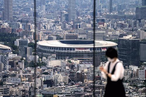 101-2 7 月10 日,日本东京,一名戴着口罩的人在东京国家体育场的观景台上拍照。
